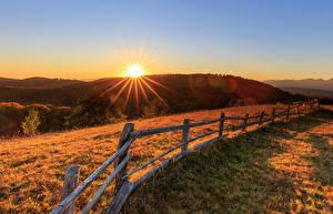 Обои для рабочего стола Луга Рассветы и закаты Забором Холм Лучи света Природа