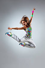 Картинки Серый фон Шатенка Прыжок Улыбка Руки Радость Девушки