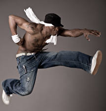 Фото Мужчины Сером фоне Кепкой Джинсы Прыгает Танцуют Рука Негры