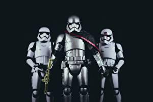 Картинка Звездные войны Солдаты Игрушки Втроем Черный фон Броня Шлем Кино