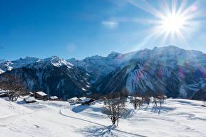Обои Швейцария Горы Зима Здания Альпы Снега Лучи света Braunwald Природа