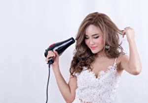 Фотография Азиаты Серый фон Шатенка Волосы Улыбается Руки Фен молодые женщины