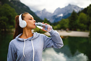 Фотографии Шатенка Наушники Бутылка Пьет воду молодая женщина
