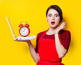 Картинки Часы Будильник Цветной фон Шатенка Ноутбуки Эмоции изумление Рука молодые женщины