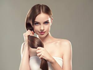 Фото Серый фон Шатенка Волосы Руки Смотрит Красивые Девушки