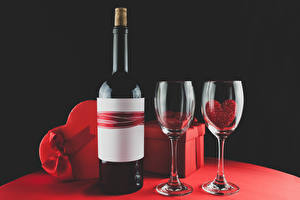 Фотография День святого Валентина Вино Черный фон Подарки Бантик Бокалы Бутылка Сердечко Еда