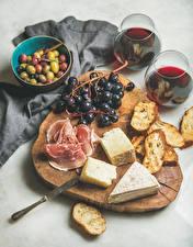 Фото Вино Виноград Оливки Сыры Ветчина Хлеб Разделочная доска Бокалы Продукты питания
