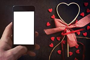 Фотографии День всех влюблённых Шаблон поздравительной открытки Сматфоном Сердечко Бантики