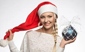 Обои для рабочего стола Рождество Шапки Шар Коса Улыбка Серый фон девушка