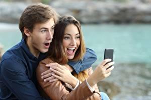 Фото Любовники Мужчины Эмоции изумление Смартфон Рука Свидании молодые женщины