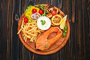 Фото Рыба Картофель фри Овощи Томаты Лимоны Лососи Разделочная доска Еда