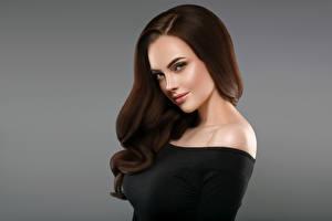 Фотографии Серый фон Шатенка Волосы Смотрит Красивая молодая женщина
