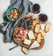 Фотографии Оливки Хлеб Сыры Ветчина Вино Сером фоне Разделочной доске Стакан Пища