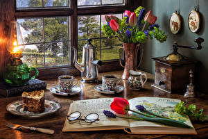 Фотографии Натюрморт Тюльпаны Гиацинты Керосиновая лампа Чайник Кофе Торты Вазы Чашка Очках Тарелке Часть Пища Цветы