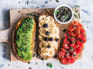 Картинки Бутерброды Томаты Бананы Авокадо Разделочной доске Втроем