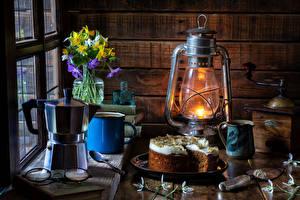 Картинка Натюрморт Керосиновая лампа Торты Чайник Подснежники Нарциссы Кружка Вазы Очки Пища