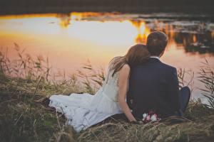Фотографии Рассвет и закат Мужчина Любовники Трава Двое Сидящие Женихом Невесты Брак молодая женщина