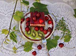 Фотография Ягоды Вишня Пирожное Скатерть Листья Тарелке Вилка столовая Нарезанные продукты Еда