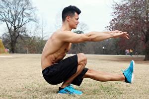 Картинка Мужчины Фитнес Тренируется Шорты Кроссовки Ног Траве Парень
