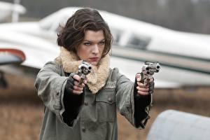 Обои для рабочего стола Milla Jovovich Пистолеты Обитель зла 4: Жизнь после смерти Револьвер Куртка Шатенка Знаменитости Девушки