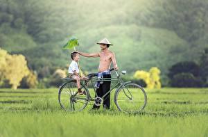 Картинка Азиатка Мужчины Траве Два Велосипед Мальчик Сидит Улыбка