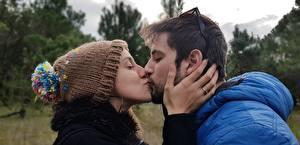 Картинка Влюбленные пары Мужчины Двое Поцелуй В шапке Очки Рука девушка