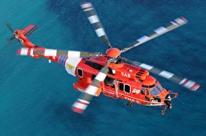 Фотографии Вертолеты Летящий Оранжевая Airbus Helicopters H225M Авиация