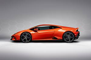 Картинка Lamborghini Оранжевый Сбоку Сером фоне Evo Huracan Автомобили