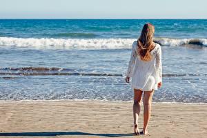 Картинки Море Волны Пляж Песка Шатенки Вид сзади Ноги молодая женщина