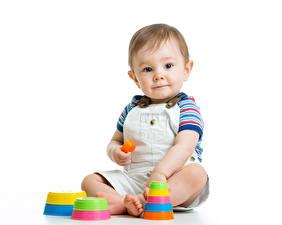 Фото Игрушка Белый фон Мальчишка Младенцы Смотрят Сидит ребёнок