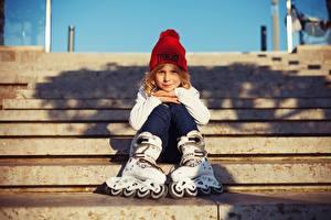Картинка Девочка Шапка Сидящие Роликовые коньки ребёнок