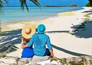 Картинки Камень Тропический Мужчина Курорты Пляже Объятие Две Шляпы Сидящие Вид сзади Природа Девушки