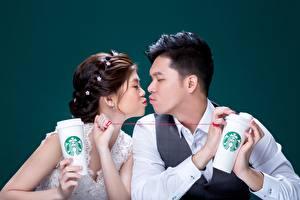 Картинка Азиатка Мужчины Влюбленные пары Цветной фон Двое Поцелуй Шатенки starbucks молодые женщины