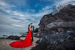 Картинка Азиатка Мужчина Скала Двое Обнимаются Платья молодые женщины