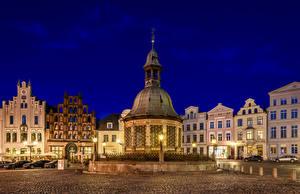 Фотографии Германия Дома Городской площади В ночи Колодец Уличные фонари Wismar Wasserkunst Города