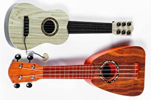 Обои Музыкальные инструменты Белом фоне Гитары Двое Ukulele