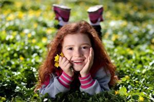 Фотография Рыжая Девочки Лежа Улыбка Траве Лица Зубы Дети