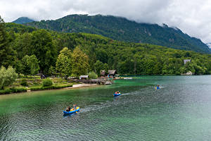 Картинка Словения Озеро Горы Леса Побережье Лодки Lake Bohinj Природа
