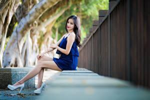 Картинка Азиаты Размытый фон Сидит Ног Шатенки Смотрит Туфли молодые женщины