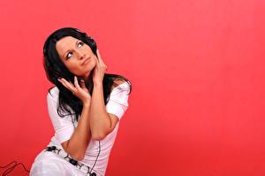 Картинка Красном фоне Брюнетки В наушниках Сидящие девушка