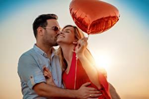 Картинка Любовники Мужчина Обнимает Целоваться Воздушным шариком Рука молодые женщины
