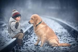 Картинки Собака Золотистый ретривер Зимние Железные дороги Мальчик Сидящие Шапка Куртке Marianna Smolina Животные