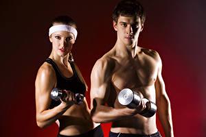 Фото Фитнес Мужчины Цветной фон Вдвоем Взгляд Гантели Спорт Девушки