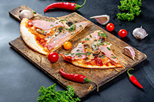 Фото Пицца Острый перец чили Томаты Чеснок Ветчина Разделочной доске Часть Пища