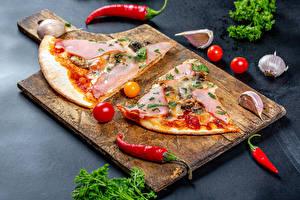 Фото Пицца Острый перец чили Помидоры Чеснок Ветчина Разделочной доске Кусок