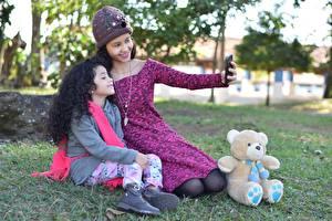 Фотографии Мишки Мать Трава Двое Брюнетки В шапке Сидящие Селфи Улыбается Девочки ребёнок
