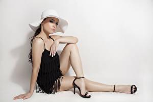 Фото Сером фоне Фотомодель Сидящие Шляпы Рука Ног девушка