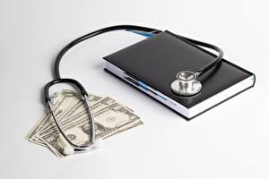 Фотографии Деньги Купюры Доллары Белым фоном Блокнот Stethoscope