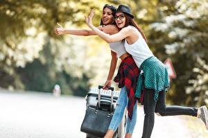 Картинки Турист Двое Шляпа Очков Смех Руки Радостный Чемоданом молодая женщина