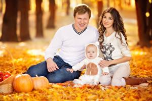Обои Осень Мама Мужчина Размытый фон Сидит Трое 3 Младенца Шатенка Взгляд Семья ребёнок Девушки